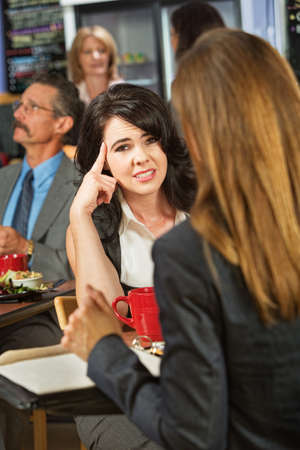 Bored woman with coworker in coffee house Stock Photo
