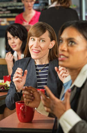 mocking: Business woman mocking coworker at table in cafeteria