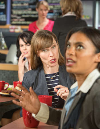 annoy: Woman bothering coworker in cafeteria at work Stock Photo