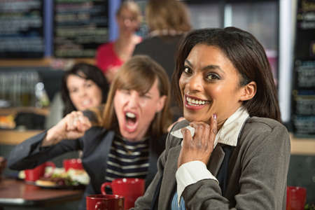 disrespectful: Angry lady behind giggling woman in coffee house Stock Photo
