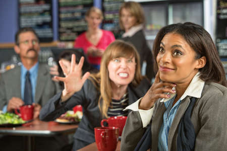 disrespectful: Annoyed coworker behind smiling business woman in cafeteria