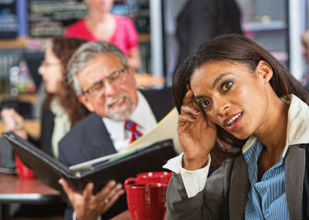 disrespectful: Bored woman next to man working during lunch break Stock Photo