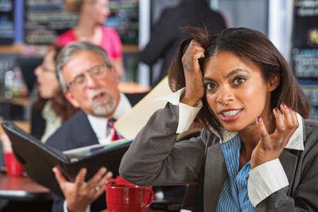 molesto: Hombre de negocios molesto leyendo para mujer tirando de su pelo