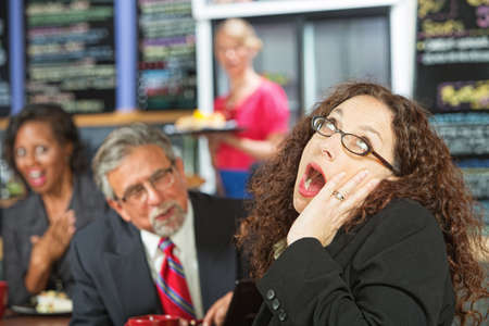 indifferent: Business woman yawning as man talks to her during lunch