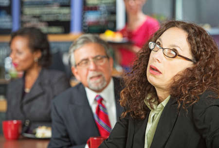 Annoyed business woman next to man in coffee house