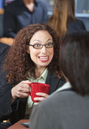 Happy business woman with red mug talking to friend photo
