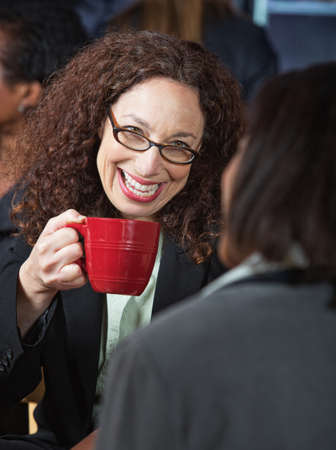 Happy woman laughing with coworker in cafeteria Foto de archivo