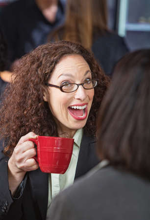 Surprised woman laughing with friend in coffee house photo