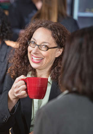 Laughing business woman with eyeglasses drinking coffee