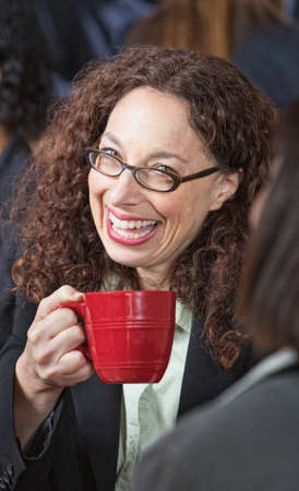 Close up of business woman with red mug laughing photo