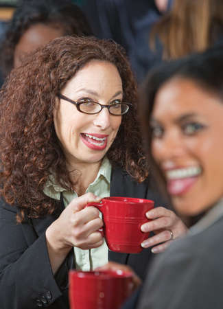 Two pretty business women laughing together in cafe Foto de archivo