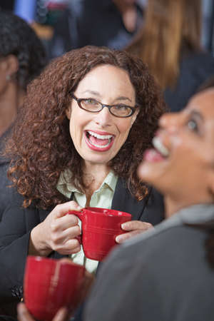 Pair of female friends laughing together in cafe photo
