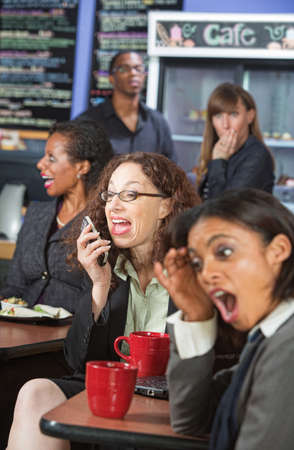 talkative: Obnoxious woman talking loudly on cell phone in cafe Stock Photo