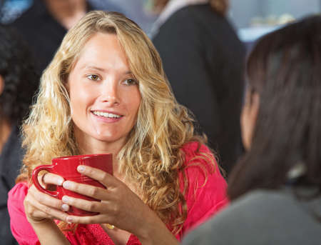 Beautiful young woman talking with friend in cafe