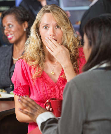 startled: Surprised Caucasian woman with hand over mouth Stock Photo