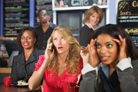 obnoxious: Loud blond woman on cell phone in restaurant Stock Photo