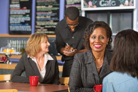 Mature smiling business woman with friend in cafe photo