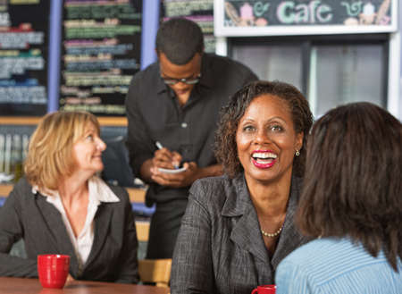 Cute laughing mature business woman with friend in cafe photo