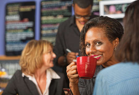 Cheerful business woman sipping beverage in cafe