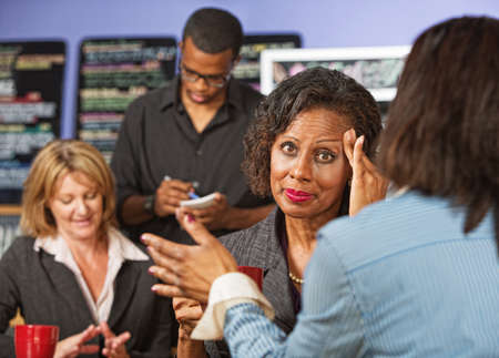 Overwhelmed female business person with headache listening to friend photo