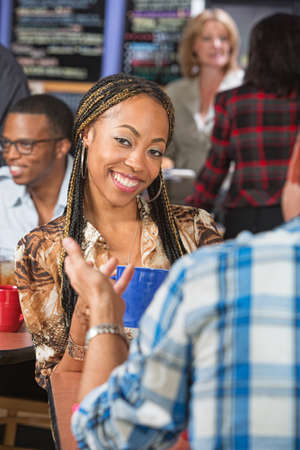 Pretty woman with braids talking with man in cafe photo