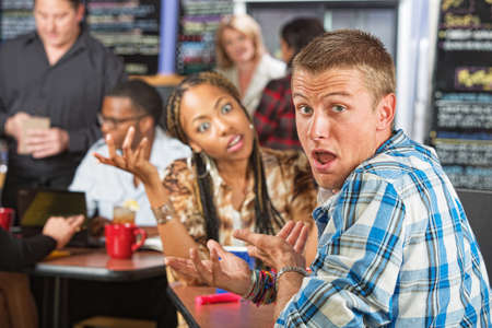 Embarrassed Caucasian man with young woman in cafe