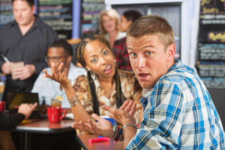 disrespectful: Bickering young married couple sitting in coffee house