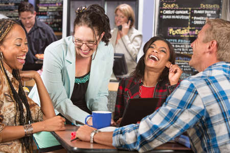Laughing group of students with laptop in cafe