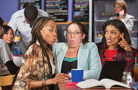 Young woman with disgusted friends studying in bistro photo