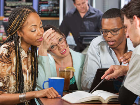 cramming: Worried young student with friends studying in cafe