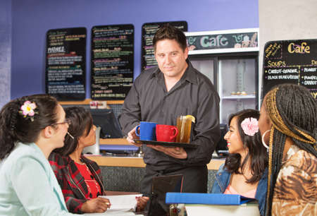 Cheerful barista serving beverages to students in cafe photo