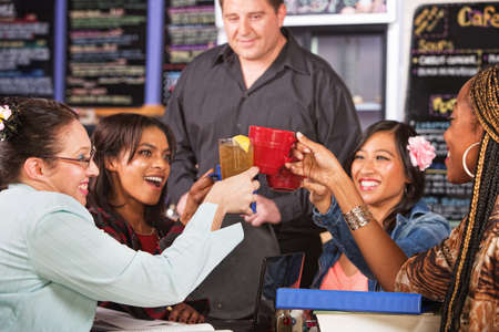 Mixed group of students toasting drinks in cafe photo