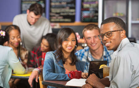 black man white woman: Handsome young African man with friends in cafe Stock Photo