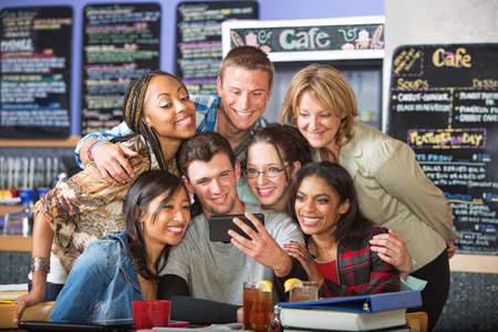 Diverse students smiling with camera phone in bistro photo