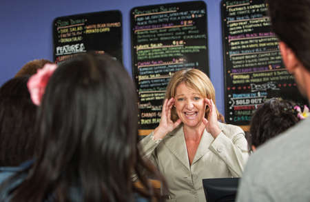 Overwhelmed coffee house owner taking orders from group