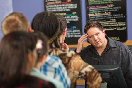 Confused barista at cash register in cafe