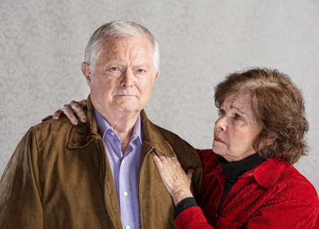forgetfulness: Concerned senior husband and wife over gray background Stock Photo