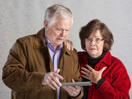 Angry man using tablet with embarrassed woman Banco de Imagens - 30479546