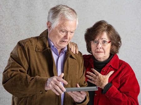 Verärgerter Mann mit Tablet mit peinlich Frau Standard-Bild - 30479546