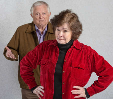 stubborn: Suspicious senior woman in front of confused man Stock Photo
