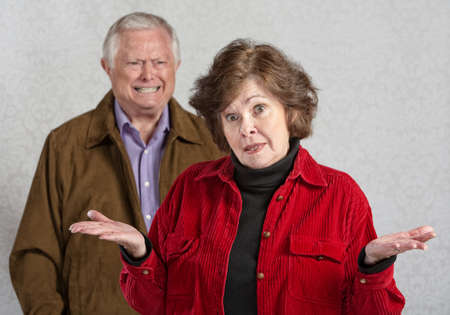 Frustrated woman with hands up and angry man
