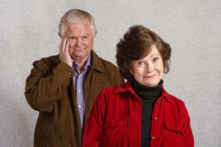 blushing: Senior male blushing while happy woman is smiling
