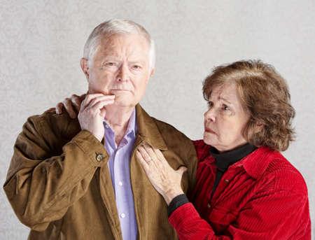 Worried wife holding concerned husband in jacket 写真素材