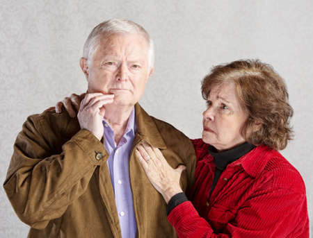 Worried wife holding concerned husband in jacket Foto de archivo