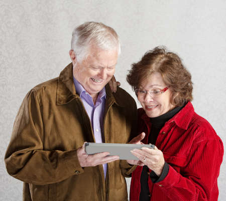 Senior male and female excited with computer tablet photo