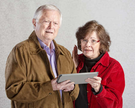 Two mature adults confused with tablet computer photo
