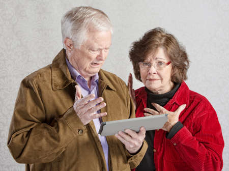 befuddled: Overwhelmed senior man and woman holding tablet
