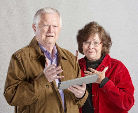 Perplexed man and woman holding computer tablet photo