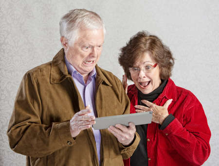 Shocked man and woman looking at computer tablet photo