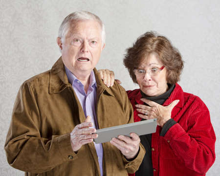Startled man and woman looking at computer tablet photo